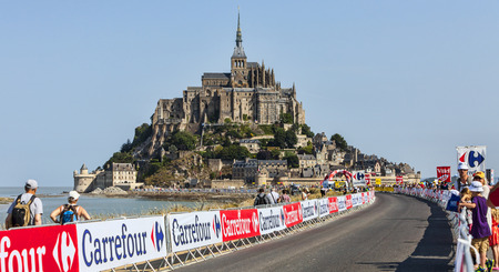 race for time: Le Mont Saint Michel,France-July 10, 2013: Spectators waiting for the start of the race on the roadside during the stage 11 of the edition 100 of Le Tour de France 2013, a time trial between Avranches and Mont Saint Michel.