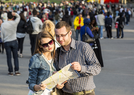 Young couple looking on a map in a crowded city street in Paris, France. photo
