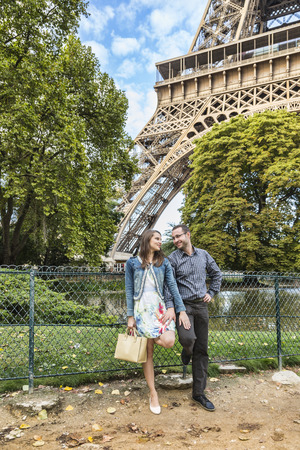 Young happy couple posing in a park close to Eiffel Tower in Paris. photo