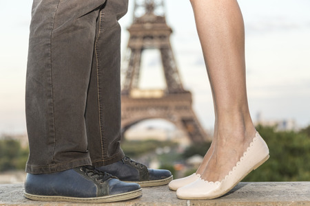 Image of the Eiffel Tower in the distance seen between the legs of a couple kissing on a esplanade