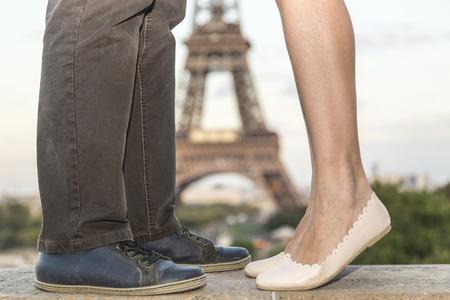 parejas: Imagen de la Torre Eiffel en la distancia vista entre las piernas de una pareja bes�ndose en una explanada