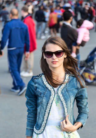 Environmental portrait of a young woman walking in a crowded street in Paris. photo