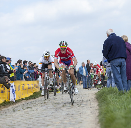carrefour: CAMPHIN EN PEVELE,FRANCE-APR 13:The peloton,containing young cyclists, riding during a race of juniors on the cobblestone sector in Camphin-en-Pevele on April 13 2014 before Paris-Roubaix cycling race Editorial