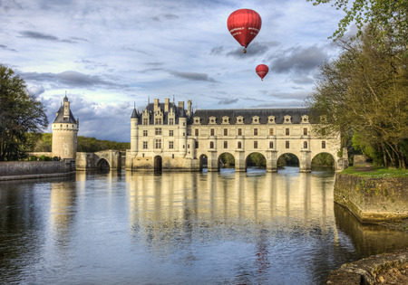 et: Chenonceaux, France- April 6, 2014: Two red hot air balloons fly above the Chenonceau Castle spanning the river Cher in the Loire Valley ,France. Editorial