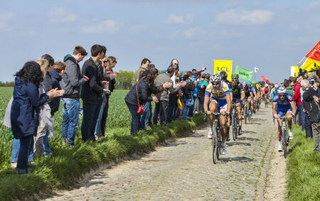 CAMPHIN EN PEVELE,FRANCE-APR 13:The peloton riding on the cobblestone sector Carrefour de lArbre in Camphin-en-Pevele on April 13 2014 during Paris-Roubaix cycling race