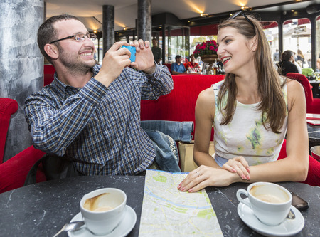Young happy couple taking photos with mobile phone in a Parisian Cafe. photo