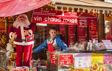 Strasbourg, France- December 24, 2012: A young boy sell traditional red hot wine and other specific products in a kiosk during the Christmas Market in Strasbourg, Alsace, France.