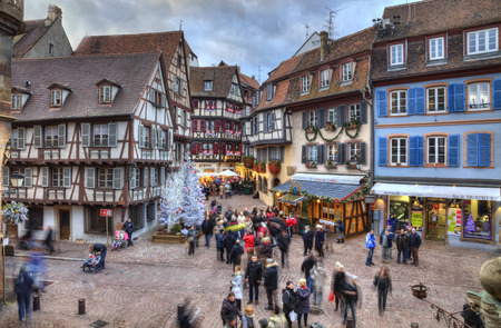 colmar: Colmar, France- Decmebr 06,2013: People walking in a town square between traditional half-timber houses and specific Christmas decoration in Colmar, Alsace, France. HDR image with selective motion blur on some of the people. Colmar is considered to be the Editorial