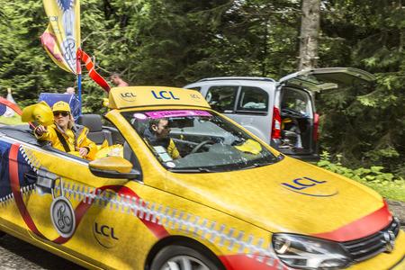 le cap: Col de Platzerwasel, Francia - 14 de julio 2014: La mujer joven tirando a cabo la promoci�n de gorras amarillas de un autom�vil durante la caravana publicitaria en la carretera de monta�a Pass Platzerwasel, en las monta�as de los Vosgos, en la etapa 10 del Tour de Francia fue 2014.LCL la l