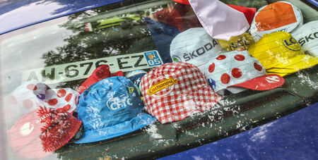 sponsors: LE BOURG- OISANS,FRANCE- JUL 18:Various caps are on the rear window of a car on the road to Alpe Huez during the stage 18 of le Tour de France on July 18, 2013. Editorial