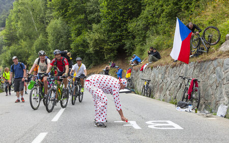 apparition: ALPE HUEZ, FRANCE, JUL 18: Unidentified people doing various activities on the road to Alpes dHuez before the apparition of the cyclists during the stage 18 of le Tour de France on July 18, 2013.