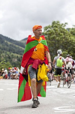 apparition: ALPE HUEZ, FRANCE, JUL 18: Basque fan of le Tour de France walking on the road to Alpes dHuez before the apparition of the cyclists during the stage 18 of le Tour de France on July 18, 2013.