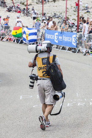 apparition: Mont Ventoux, France- July 14 2013: Unidentified professional photographer carrying heavy equipment on the road to Mount Ventoux before the apparition of the competitors during the stage 15 of the 100 edition of Le Tour de France 2013.