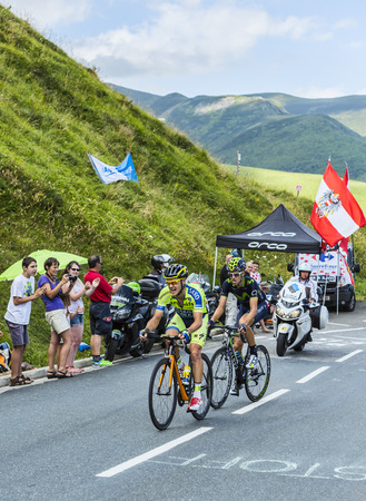 Col de Peyresourde,France- July 23, 2014: The cyclists Nicolas Roche ( Team Tinkoff-Saxo ) and Jesus Herrada Lopez (MovistarTeam) climbing the road to Col de Peyresourde in Pyrenees Mountains during the stage 17 of Le Tour de France on 23 July 2014. Editorial
