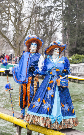 disguised: Annecy, France, February 23, 2013: Couple disguised in beautiful costumes posing near the lake in Annecy, France,  during a Venetian Carnival which is held yearly to celebrate the beauty of the real Venice.