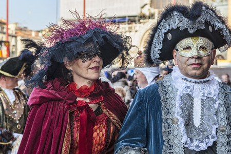 18th: Venice, Italy- February 18th, 2012: Portrait of a disguised couple posing in the crowded Sam Marco square during the Venice Carnival days.