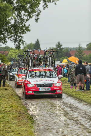apparition: Ennevelin, France - July 09,2014: The techinical car of the Team Cofidis driving on the cobblestoned road from Ennevelin in North of France, on a rainy weather, before the apparition of the peloton in the 5 of Le Tour de France 2014.