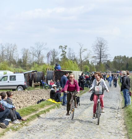 arbre: CAMPHIN EN PEVELE,FRANCE-APR 13: Two casual women cycling on the cobblestone sector Carrefour de Arbre in Camphin-en-Pevele on April 13 2014 during Paris-Roubaix cycling race