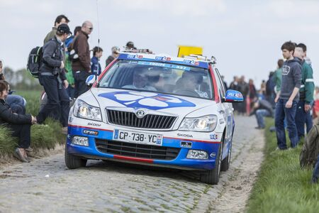 arbre: CAMPHIN EN PEVELE,FRANCE-APR 13:The official car of FDJ team driving on the cobblestone sector Carrefour de Arbre in Camphin-en-Pevele on April 13 2014 during Paris-Roubaix cycling race
