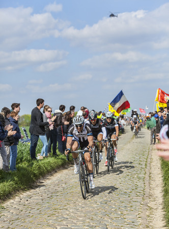 arbre: CAMPHIN EN PEVELE,FRANCE-APR 13:Three cyclists ( Degenkolb,Cancellara,Stybar) riding on the cobblestone sector Carrefour de Arbre in Camphin-en-Pevele on April 13 2014 during Paris-Roubaix race