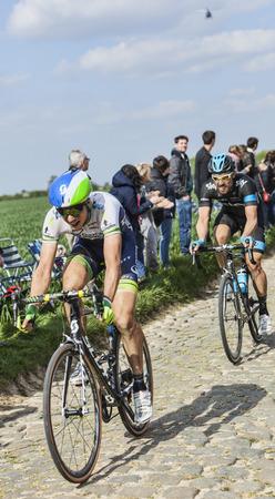 carrefour: CAMPHIN EN PEVELE,FRANCE-APR 13: Two cyclists (Jens Keukeleire, Bernhard Eisel) riding on the cobblestone sector Carrefour de Arbre in Camphin-en-Pevele on April 13 2014 during Paris-Roubaix race