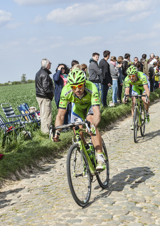 arbre: CAMPHIN EN PEVELE,FRANCE-APR 13:Two cyclists (Kristijan Koren and Maciej Bodnar) riding on the cobblestone sector Carrefour de Arbre in Camphin-en-Pevele on April 13 2014 during Paris-Roubaix race