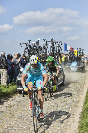 arbre: CAMPHIN EN PEVELE,FRANCE-APR 13:Two cyclists (Borut Bozic, Alexandre Pichot) riding on the cobblestone sector Carrefour de Arbre in Camphin-en-Pevele on April 13 2014 during Paris-Roubaix race Editorial