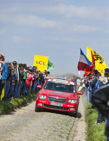 arbre: CAMPHIN EN PEVELE,FRANCE-APR 13:Official red car transporting the finished judges on the cobblestone sector Carrefour de Arbre in Camphin-en-Pevele on April 13 2014 during Paris-Roubaix race Editorial