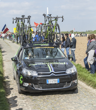 arbre: CAMPHIN EN PEVELE,FRANCE-APR 13:The car of Cannondale team carrying spare bicycles on the cobblestone sector Carrefour de Arbre in Camphin-en-Pevele on April 13 2014 during Paris-Roubaix race