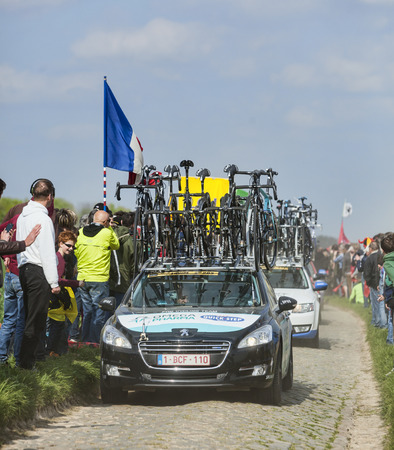 arbre: CAMPHIN EN PEVELE,FRANCE-APR 13:The car of Omega Pahrma Quick Step carrying spare bicycles on the cobblestone sector Carrefour de Arbre in Camphin-en-Pevele on April 13 2014 during Paris-Roubaix race
