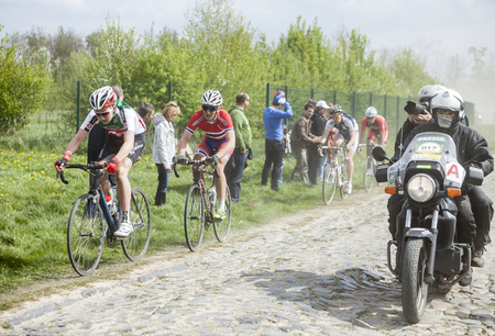 arbre: CAMPHIN EN PEVELE,FRANCE-APR 13: The peloton,containing young cyclists,and photographers bike riding during a race of juniors on the cobblestoned road in the dust, few hours before the famous official one day race Paris - Roubaix. Editorial