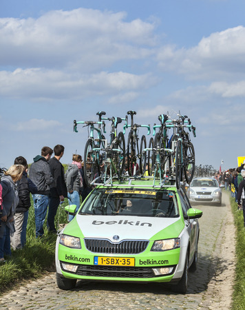 arbre: CAMPHIN EN PEVELE,FRANCE-APR 13: The official car of Belkinteam carrying spare bicycles in front of spectators on the famous cobblestone sector Carrefour de Arbre in Camphin-en-Pevele town during the 2014 edition of Paris-Roubaix cycling race.