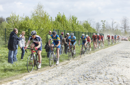 carrefour: CAMPHIN EN PEVELE,FRANCE-APR 13:The peloton,containing young cyclists, riding during a race of juniors on the cobblestoned road in the dust, few hours before the famous official one day race Paris - Roubaix. Editorial