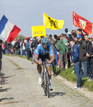 carrefour: CAMPHIN EN PEVELE,FRANCE-APR 13:The New Zealand cyclist Jack Bauer from Garmin-Sharp Team riding on the famous cobblestone sector Carrefour de Arbre in Camphin-en-P?v?le town during the 2014 edition of Paris-Roubaix cycling race. Editorial