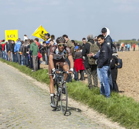 arbre: CAMPHIN EN PEVELE,FRANCE-APR 13:The French cyclist Damien Gaudin from Ag2r-La Mondiale Team riding on the famous cobblestone sector Carrefour de Arbre in Camphin-en-P?v?le town during the 2014 edition of Paris-Roubaix cycling race.