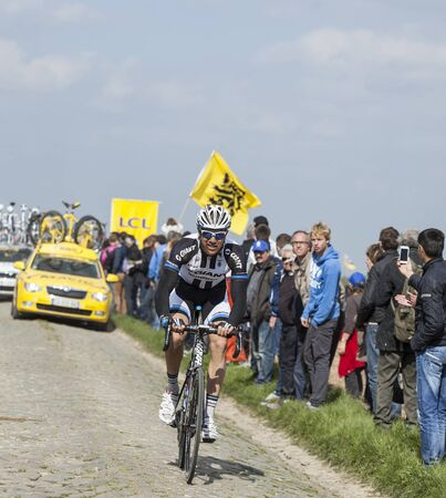 arbre: CAMPHIN EN PEVELE,FRANCE-APR 13:The German cyclist Nikias Arndt from Giant Shimano Team riding on the famous cobblestone sector Carrefour de Arbre in Camphin-en-P?v?le town during the 2014 edition of Paris-Roubaix cycling race. Editorial