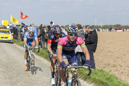 arbre: CAMPHIN EN PEVELE,FRANCE-APR 13:The Italian cyclist Andrea Palini from Lampre Merida Team riding on the famous cobblestone sector Carrefour de Arbre in Camphin-en-P?v?le town during the 2014 edition of Paris-Roubaix cycling race. Editorial