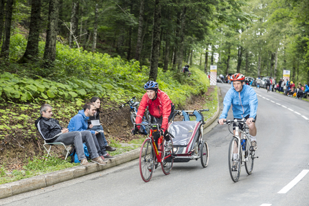 apparition: Le Markstein, France- July 13, 2014: Unidentified couple carrying their child climb on bicycles the road to mountain pass Le Markstein, before the apparition of the peloton, during the stage 9 of Le Tour de France 2014. Editorial