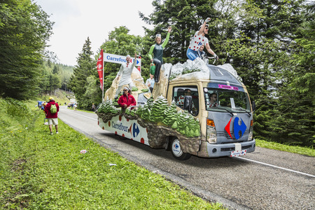 le cap: Col de Platzerwasel, France - July 14, 2014:People throwing traditional Polka Dot caps from the fancy truck of Carrefour during the passing of the advertising caravan on the road to route to the mountain pass Platzerwasel during the stage 10 of Le Tour de