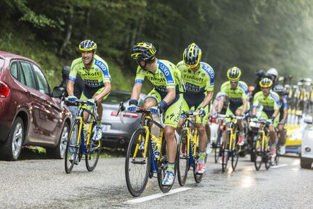 alberto: Col du Platzerwasel, France - July 14, 2014: Members of the Team Thinkoff - Saxo help Alberto Contador to climb the road to mountain pass Platzerwasel in Vosges mountains, during the stage 10 of Le Tour de France 2014. Inside this group Contador rides wit