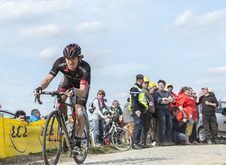 carrefour: Carrefour de lArbre,France - April 12,2015: The New Zealand cyclist, Shane Archbold of Bora-Argon 18 Team, overcome a very tough crash and finished his first ever senior Paris-Roubaix race. Here he is pedaling in the famous sector Careffour de lArbre.