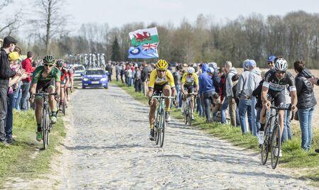 carrefour: Carrefour de lArbre,France - April 12,2015: Group of cyclists riding on the famous cobblestoned road from Carrefour de lArbre during the Pris Roubaix race 2015.