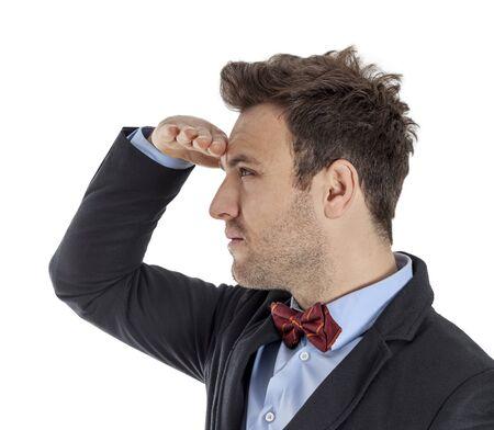 lejos: Perfil de un hombre joven y guapo con un lazo rojo que mira en la distancia contra un blanco.