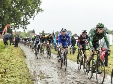 peloton: Ennevelin, France - July 09,2014: The peloton riding on a cobbled road during the stage 5 of Le Tour de France 2014.