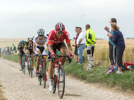 bystanders: Quievy,France - July 07, 2015: Group of four cyclists riding on a cobblestoned road during the stage 4 of Le Tour de France 2015 in Quievy, France, on 07 July,2015.