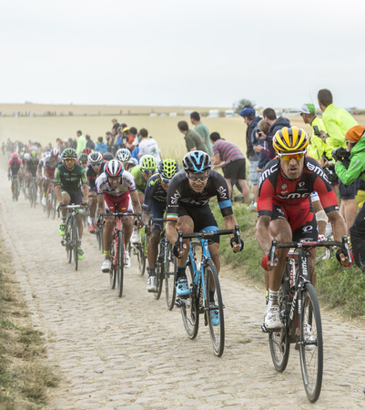 bystanders: Quievy,France - July 07, 2015: Manuel Quinziato BMC Team and Nicolas Roche Team Sky riding in front of a cyclists on cobblestoned road during the stage 4 of Le Tour de France 2015 in Quievy, France, on 07 July,2015.