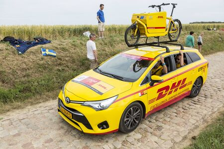 entertainment event: Quievy,France - July 07, 2015: DHLvehicle during the passing of the Publicity Caravan on a cobblestoned road in the stage 4 of Le Tour de France on July 7 2015 in Quievy, France. DHL is the global market leader in the logistics industry.