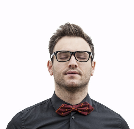eye closed: Frontal portrait of a young man with glasses with his eye closed, isolated against a white background. Stock Photo