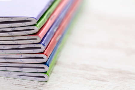 notebooks: Close-up image of a stack of colorful notebooks on a white wooden table. Selective focus.