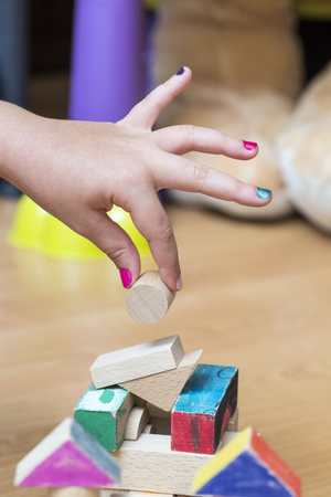 play room: Close-up of a little girls hand building something using wooden geometrical pieces, in her play room.